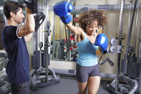woman boxing gloves: African American woman has aboxing workout with an Asian man