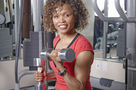 African American woman doing bicep curls in a gym Stock Photo