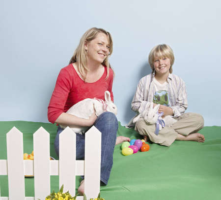 Mother and son sitting with pet rabbits Stock Photo