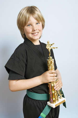 Young boy in a karate outfit holding a trophy Stock Photo