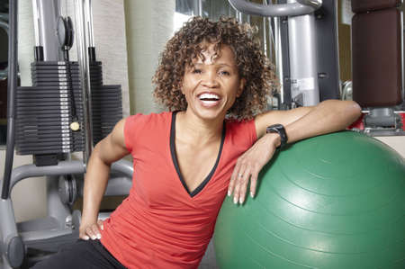 frizzy hair: Smiling African American woman resting against a fitness ball in the gym