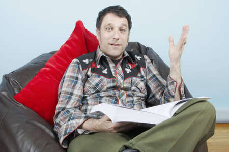 A man sitting in a leather beanbag with a book that seems to have just given him the information he has been searching for