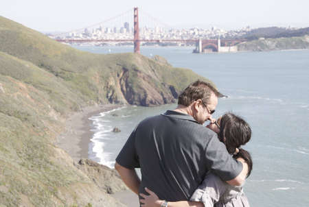 An affectionate couple on vacation enjoying the view of the Golden Gate Bridge and San Franciscos cityscape Stock Photo