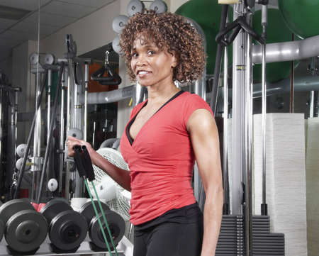 frizzy hair: African American woman wearing a red doing arm exercises in the gym