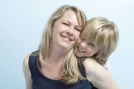 Head and shoulders image of a blond woman with her blond son nestling his chin on her shoulder. Stock Photo