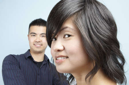Headshot of a Young Asian female with a young Asian male in the background