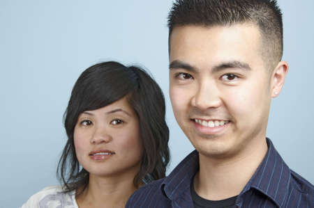 Headshot of a Young Asian male with a young Asian female in the background