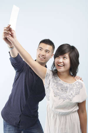 A delighted Asian couple holding and blank card up into the air together Stock Photo