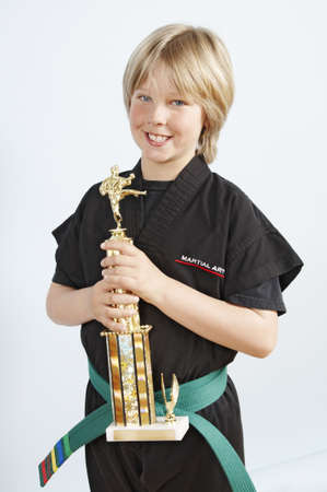 Blond boy in his black karate gi holding his trophy Stock Photo