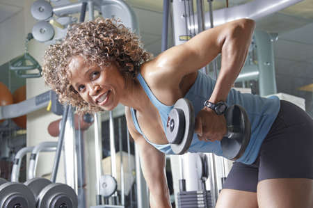 An African American woman working out in the gym with weights photo