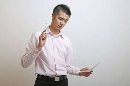 Asian office worker considering how to act on the information he has just read Stock Photo