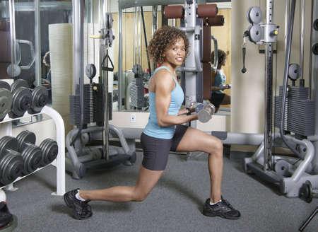 lunges: Mujer que trabaja las embestidas y bucles con pesos en un gimnasio