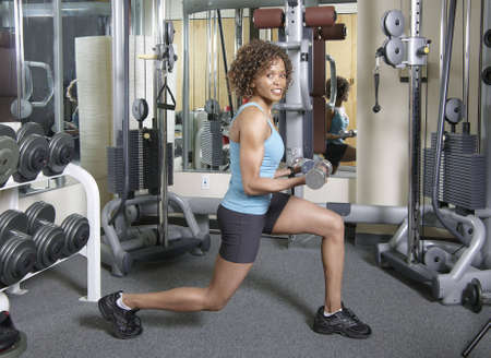 Woman working out doing lunges and curls with weights in a gym photo