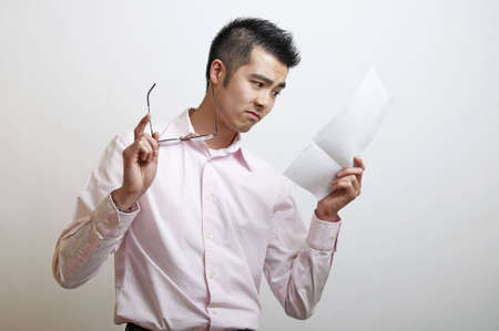 A young Asian man reading at something that causes concern.