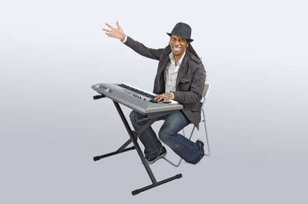 African American man seating and playing an electronic keyboard