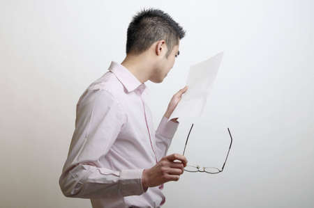 Head and shoulders of an Asian man looking at a letter that has been left blank. Stock Photo