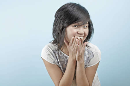 A young Asian woman smiles with her hands by her mouth in a cute pose