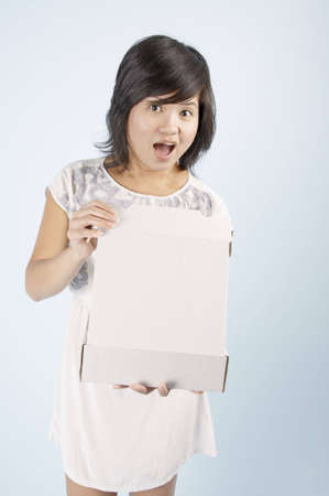 A young Asian woman showing happy surprise holding an open box which has been left blank for customization photo