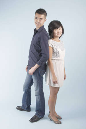 A young Asian couple standing together back to back and smiling photo