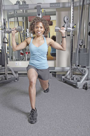 African American woman working out in a gym doing lunges and holding dumbbells up at her shoulders
