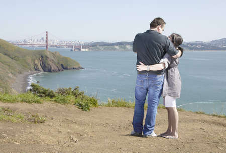 A couple share a tender moment while taking in a view of San Francisco and the Golden Gate bridge.