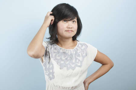 A young Asian woman scratching her head while in thought Stock Photo