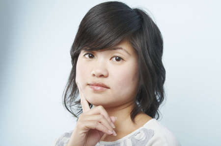 Headshot of a young Asian woman with a finger on her cheek