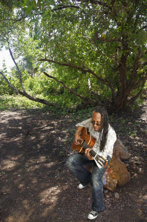 African American man playing acoustic guitar under a tree