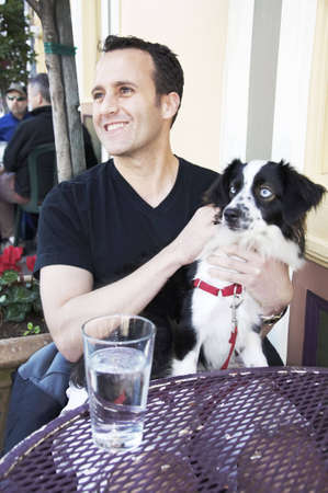 Caucasian man sitting at a street cafe table with his pet dog on his lap