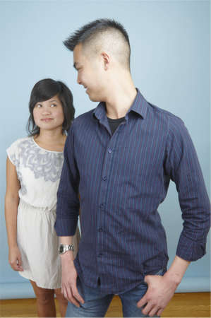 Asian man and woman standing together and smiling at each other photo