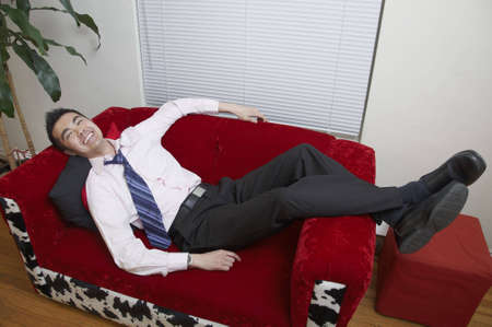 A young Asian office worker relaxes on his couch at home