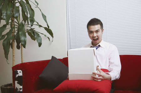 An Asian man surprised and delighted when he opens his package Stock Photo - 6999014