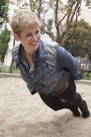 A woman playing on a swing in a sand pit