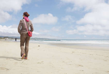 sheepskin: Fully dressed woman walking on a beach away from camera Stock Photo