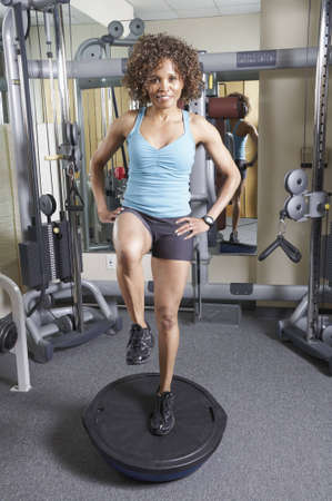 Woman on a balance trainer exercising in the gym photo