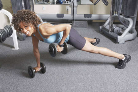 African American woman doing floor exercises with free weights photo