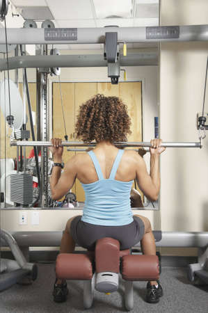 Back view of an African American woman doing seated bar exercises at a gym photo
