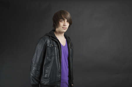 A young adult upper body pose wearing a leather jacket