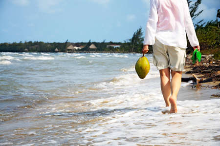 An anonymous woman walking along the beach carrying a freshly picked coconut and sandals