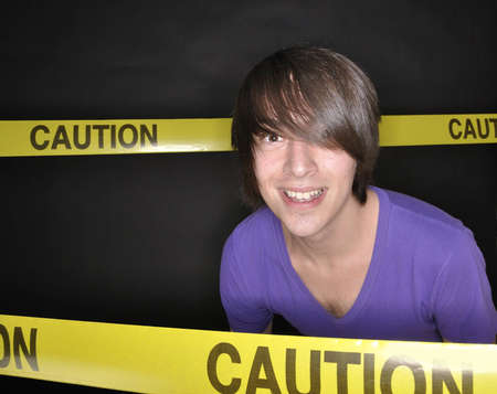 Young man with an uneasy smile surrounded by caution tape