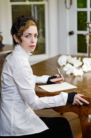 Woman sitting at a table ready to do some writing Stock Photo