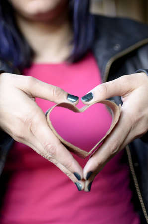 a woman holding a heart formed with the insulating sleeve from a coffee cup