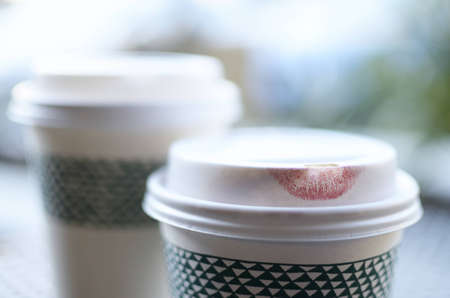 lipstick imprint on the lid of a disposable coffee cup