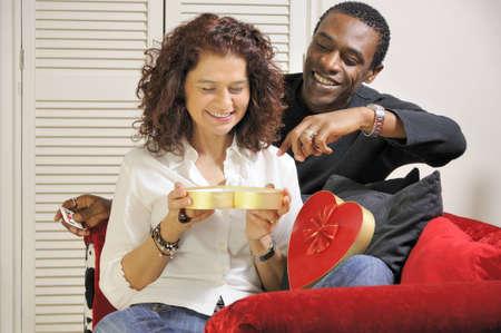 A mixed race couple enjoying chocolates together