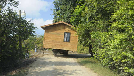 transporting: Wooden house being transported along a narrow road