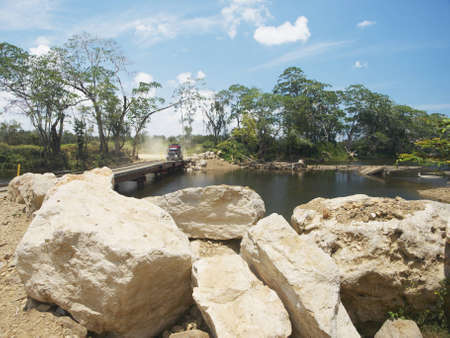 A large truck about to cross a river on the temporary Kendal Bridge in Belize