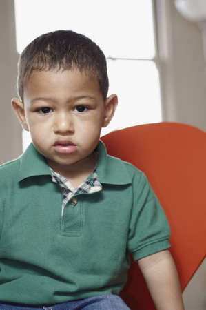 Mixed race toddler sitting and looking sullen