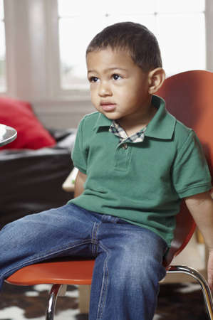 Mixed race infant seated on a chair Stock Photo