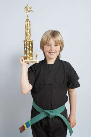 Young karate boy proudly showing off his trophy