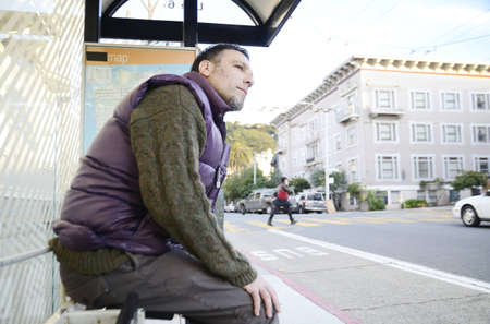 A man dressed in warm clothes waiting at a bus stop